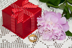 Red gift box with golden ring and peony Stock Photography