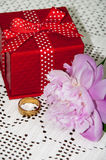 Red gift box with golden ring and peony Royalty Free Stock Image