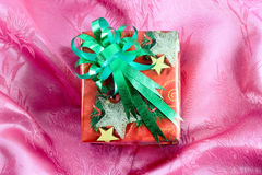 Red gift box with green ribbon. On pink satin Royalty Free Stock Photo