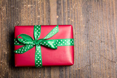 Red gift box with green ribbon with polka dots on a wood backgro Royalty Free Stock Images