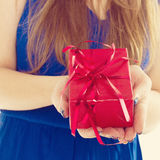 Red gift box with hands of a young woman Stock Images