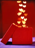 Red gift box with the heart golden light bokeh drop in.Valentine Royalty Free Stock Photography