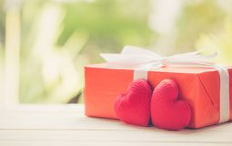 Red gift box and heart shape on wood table top with nature green blur bokeh background Royalty Free Stock Image
