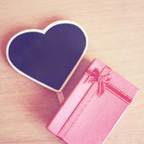 Red gift box and heart shaped blackboard Royalty Free Stock Photography