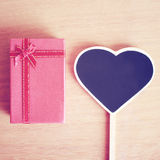 Red gift box and heart shaped blackboard with copy space Stock Photography