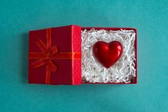 Red gift box with heart by Valentine`s day on blue background. Giving heart love concept royalty free stock images