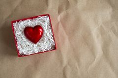 Red gift box with heart by Valentine`s day on craft paper. Giving heart love concept, copy space stock photography