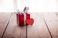Red gift box and heart on white wooden table Royalty Free Stock Photography