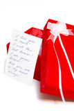 Red gift box with love card. Red gift box with a card next to it with a love message written on the card stock image