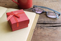 Red gift box with notebook and cup of coffee Royalty Free Stock Image