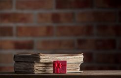 Red gift box and old books. On wooden table at brick wall background. Library Royalty Free Stock Photo