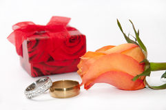 Red gift box with pair of engagement rings and orange rose Stock Photo