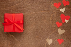 Red gift box and paper hearts. On wooden background Royalty Free Stock Photos