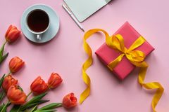 Red gift box on pink background. Background with coffee, laptop and flowers. royalty free stock photos