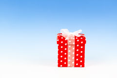 Red gift box, polka dots. With bow on blue background royalty free stock image