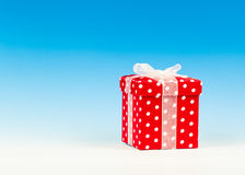 Red gift box. Polka dots with bow on blue background royalty free stock image
