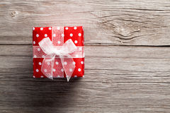 Red gift box, polka dots. On wood background royalty free stock image
