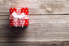 Red gift box, polka dots. On wood background stock photography