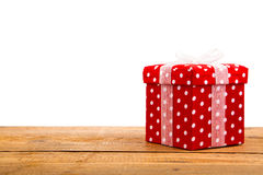 Red gift box, polka dots, on wood background Stock Images