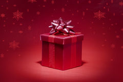 Red gift box on red background with snowfall Royalty Free Stock Photography