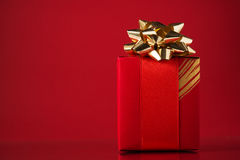 Red gift box on red background with space for text. Merry christmas card. Stock Image