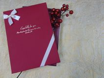 Red gift box with a red branch on beige crumpled paper. Red gift box large with an inscription with a branch of red berries is on beige crumpled paper Stock Photo