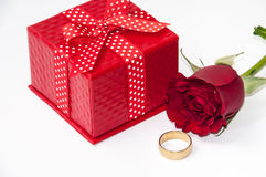 Red gift box with a red rose and golden ring Stock Images