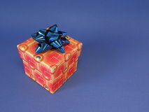 Red gift box and ribbon. Isolated on blue Royalty Free Stock Photography