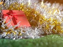 Red gift box with red ribbon bow and golden seam place on silver and gold rainbow glowing decoration background on green grass. Christmas and New year concept Royalty Free Stock Images