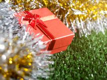 Red gift box with red ribbon bow and golden seam place on silver and gold rainbow glowing decoration background on green grass. Christmas and New year concept Royalty Free Stock Photo