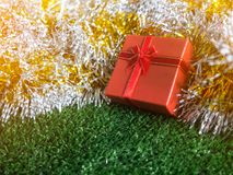 Red gift box with red ribbon bow and golden seam place on silver and gold rainbow glowing decoration background on green grass. Christmas and New year concept Stock Photography