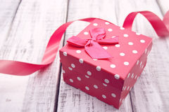 Red gift box with ribbon on rustic white wooden table. Valentine Stock Images