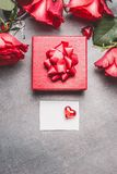 Red gift box with roses and blank paper card and heart, top view. Mock up for greeting royalty free stock photography