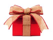 Red gift box with rustic burlap bow and ribbon Royalty Free Stock Images