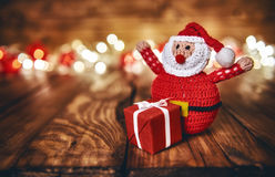 Red gift box, Santa Claus and Christmas garland. Lights on wooden rustic background Royalty Free Stock Images