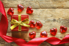 Red gift box, scarlet silk ribbon, transparent hearts Stock Photography
