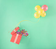 Red gift box with and set of balloons. On a light background. Colorful celebration background. Flat lay Royalty Free Stock Image