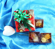 Red gift box set with green ribbon. On blue satin Stock Image