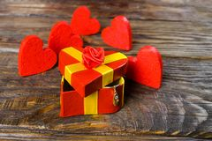 Red gift box in the shape of a heart ajar, and from it hangs a pendant in the shape of a wooden Shoe with briliant it stands on a royalty free stock photo