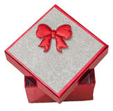 Red gift box with shinny silver cover and red bow, close up, isolated. Royalty Free Stock Image