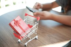 Red gift box on shopping cart with women using mobile phone royalty free stock photography