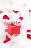 Red Gift box with silver bow on wedding veil. With rose petals Stock Photography
