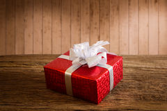 Red gift box. With silver ribbon on wooden table with Multicolor bokeh background Royalty Free Stock Images