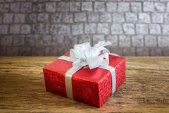 Red gift box. With silver ribbon on wooden table with Multicolor bokeh background Stock Images