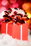 Red gift box on snow Stock Photography