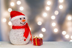 Red gift box and snowman. Snowman with red gift box on lights background Stock Image