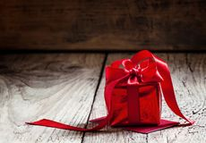 Red gift box tied with a scarlet ribbon with a bow on the old wooden background, standing on the red greeting card, selective. Focus stock photos