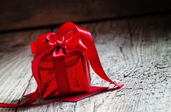 Red gift box tied with a scarlet ribbon with a bow on the old wooden background, standing on the red greeting card, selective. Focus stock images