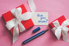 Red gift box tied with a white ribbon, markers and a card with an inscription `love you, mom!` on a pink background. The process of preparing a gift for mother royalty free stock image