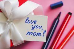 Red gift box tied with a white ribbon, markers and a card with an inscription `love you, mom!` on a pink background. royalty free stock image